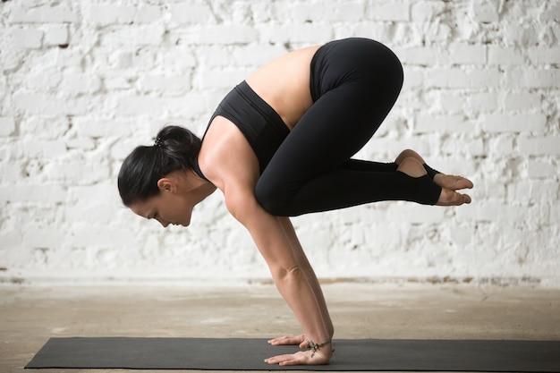 Young yogi attractive woman in bakasana pose, white loft backgro Free Photo