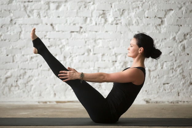 Young yogi attractive woman in paripurna navasana pose, white ba Free Photo