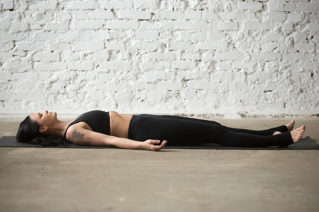 Young yogi attractive woman in savasana pose, white loft backgro Free Photo