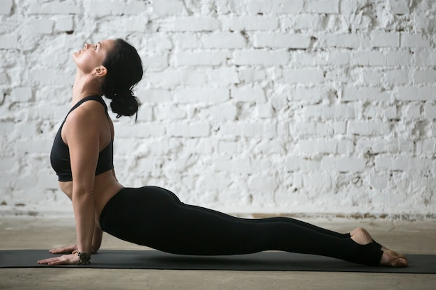 Young yogi attractive woman in upward facing dog pose, studio Free Photo