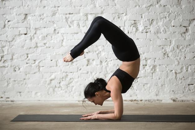 Young yogi attractive woman in vrischikasana pose, white loft ba Free Photo