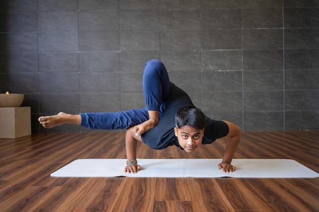 Young yogi doing astavakrasana exercise in gym Free Photo