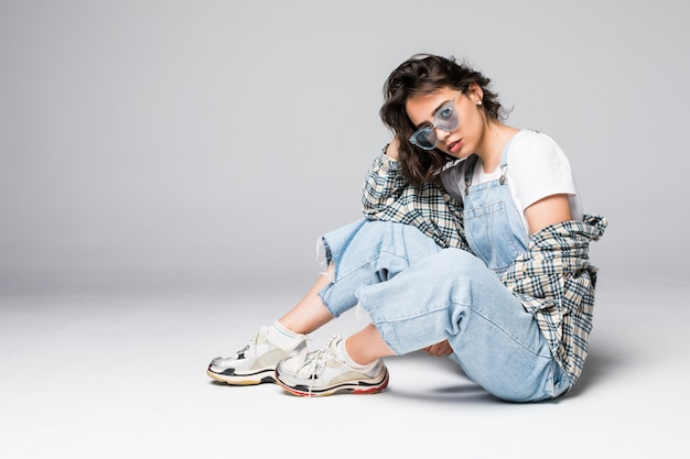 Young young female in casual clothes sitting on the floor posing over grey wall copy space Free Photo