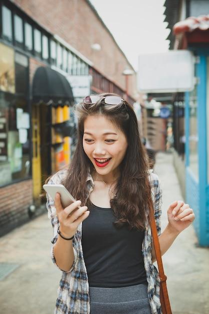 행복 얼굴 스마트 폰에서 메시지를 읽는 젊은 아시아 여성 프리미엄 사진