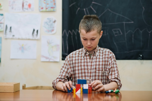 Youngster in classroom with puzzle as teaching aid