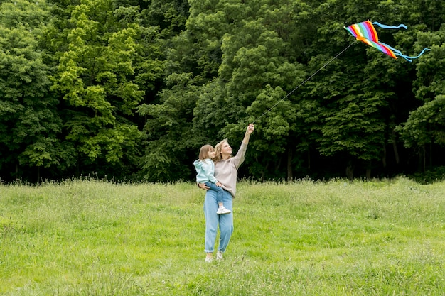 Youngster outdoors and mom playing with kite Free Photo