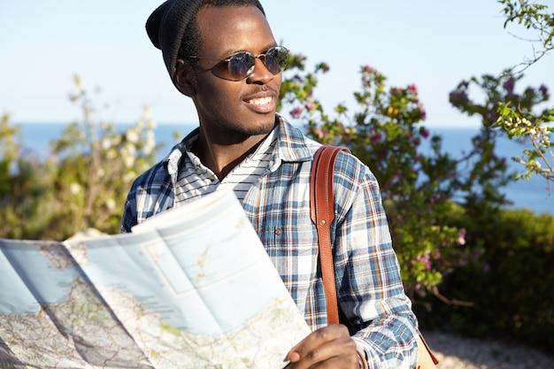Giovani, stile di vita e viaggi. viaggiatore maschio dalla pelle scura in occhiali da sole e zaino che tiene il programma di strada godendo il suo viaggio Foto Gratuite