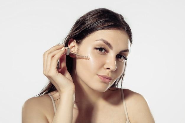 Молодежные секреты. красивая молодая женщина над белой стеной. косметика и макияж, натуральные и эко-процедуры, уход за кожей. Бесплатные Фотографии