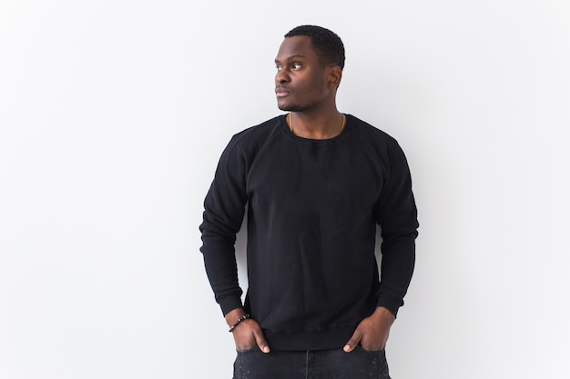 Youth street fashion concept - portrait of confident sexy black man in stylish sweatshirt on white Premium Photo