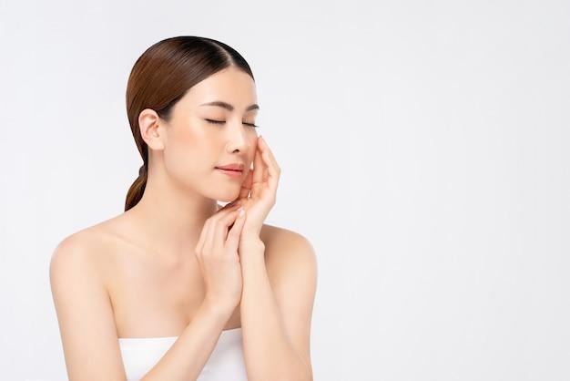 顔と目を閉じて触れる手で若々しい明るい肌アジアの女性 Premium写真