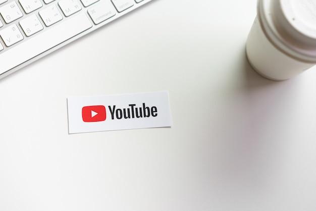 手が画面を押すと紙ラベルにyoutubeアプリのアイコンが表示されます。 youtubeは人気のあるオンラインビデオ共有webサイトです。 Premium写真