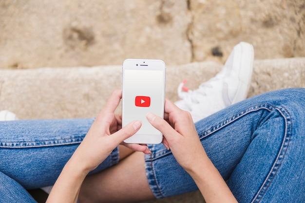 女性は携帯電話でyoutubeアプリを使用して 無料写真