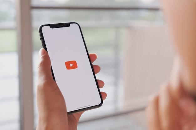 Женщина держит смартфон с социальным интернет-сервисом youtube на экране Premium Фотографии