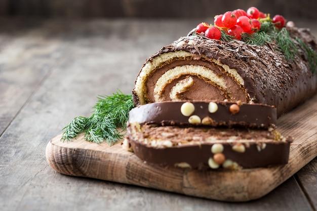 木製コピースペースに赤スグリとチョコレートyuleログケーキ Premium写真