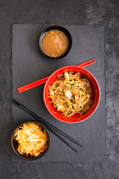 Yummy chicken noodles with soup and salad over black slate stone Free Photo