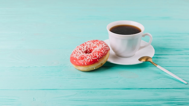 Yummy donut with cup of tea and spoon on green table Free Photo