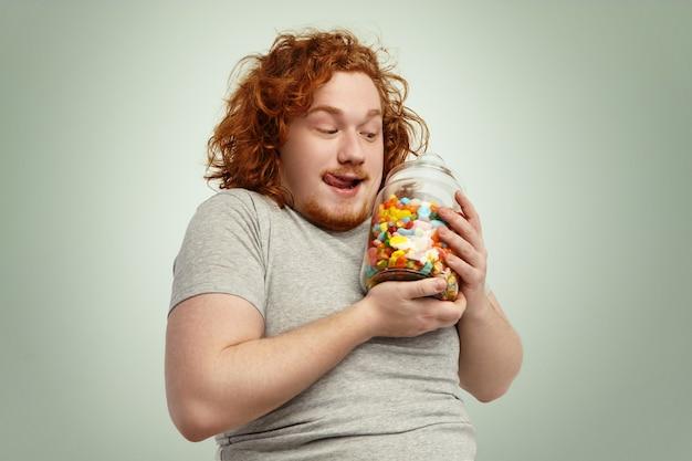 Yummy! uomo grassoccio divertente emozionante che tiene barattolo di vetro di dolci e marmellate avendo anticipato lo sguardo, leccandosi le labbra. concetto di persone, cibo, nutrizione, dieta, obesità e gola Foto Gratuite