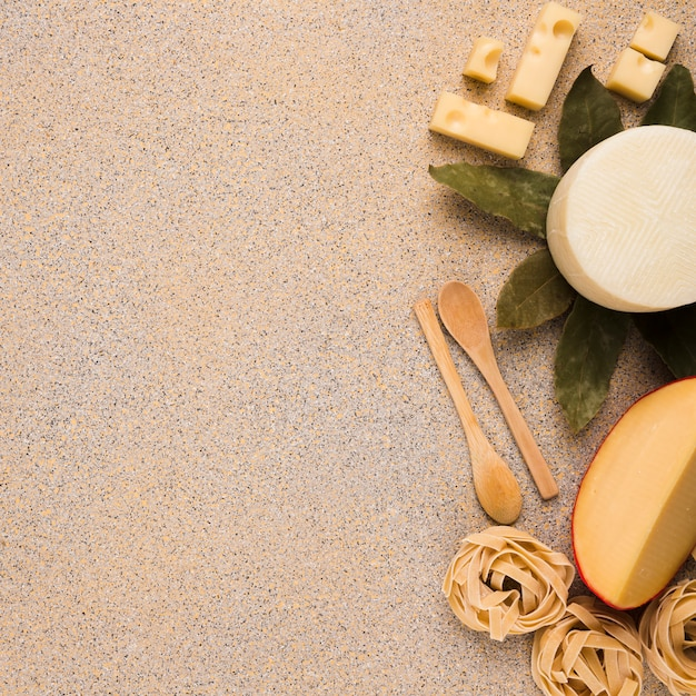Yummy fresh types of cheeses with raw pasta ; bay leaves and wooden spoon over marble texture surface Free Photo