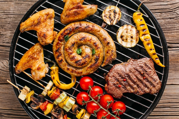 Yummy grilled spiral sausages and meat with vegetable on barbecue grill Free Photo
