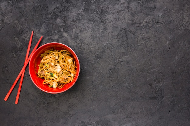 Yummy japanese chicken noodles in red bowl with chopsticks over textured black slate Free Photo