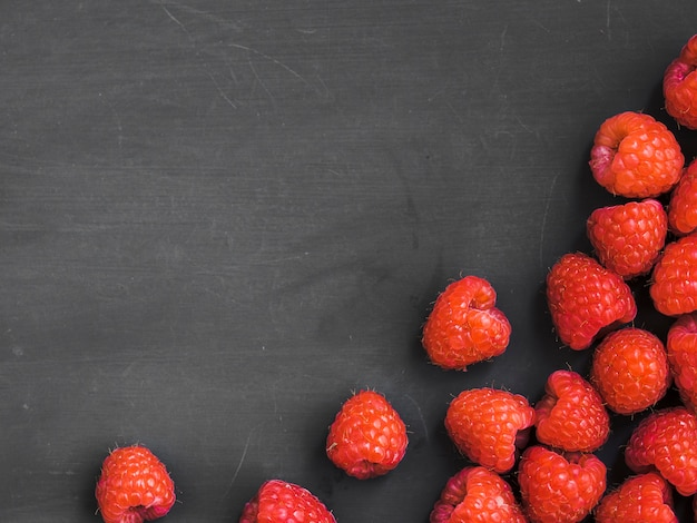 Yummy raspberries on dark surface Free Photo