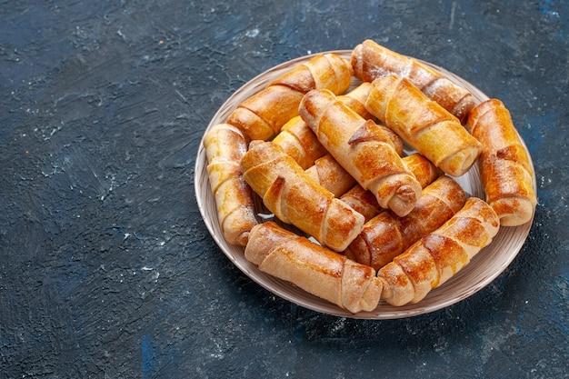 Вкусные сладкие браслеты с начинкой на тарелке на темном столе, выпечка из сладкого бисквитного торта Бесплатные Фотографии