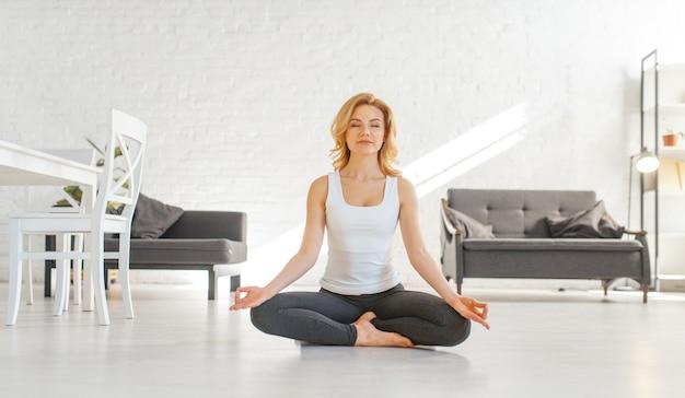 Юонг женщина сидит на полу в позе йоги, интерьер гостиной в белых тонах Premium Фотографии