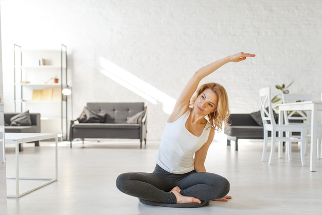 Юонг женщина сидит на полу в позе йоги Premium Фотографии