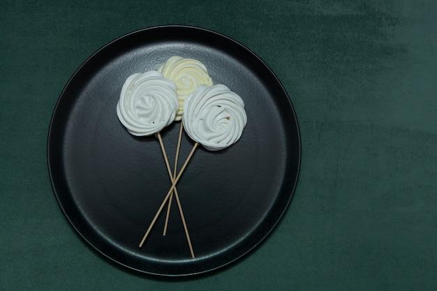 黒いプレートにゼファーまたはマシュマロ。バレンタインや母の日のスティックやオリジナルの甘い花束の美しいメレンゲ。 Premium写真