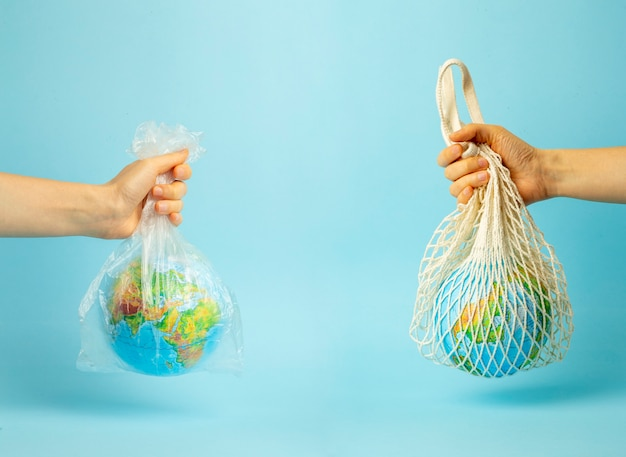 Zero waste concept. string bag and plastic bag in a female hand with earth globe. plastic bags free Premium Photo