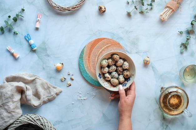 大理石のテーブルにゼロ廃棄物のイースターの背景。ウズラのイースターエッグと春の自然の飾りとユーカリの小枝。 Premium写真