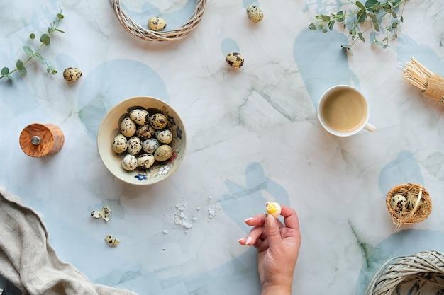 大理石のテーブルにゼロ廃棄物のイースターの背景。ウズラのイースターエッグと春の自然の装飾、小枝、ユーカリ。 Premium写真
