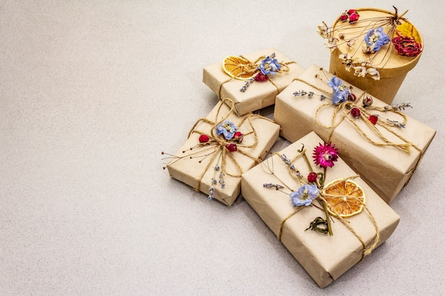Zero waste gift concept. birthday eco friendly packaging. festive boxes in craft paper with different organic decorations. Premium Photo