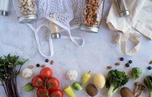 Нулевой ненужный образ жизни. хлопок чистая сумка со свежими овощами и устойчивой стеклянной банкой на цементном фоне плоского положения без пластика для покупки продуктов и доставки. Premium Фотографии