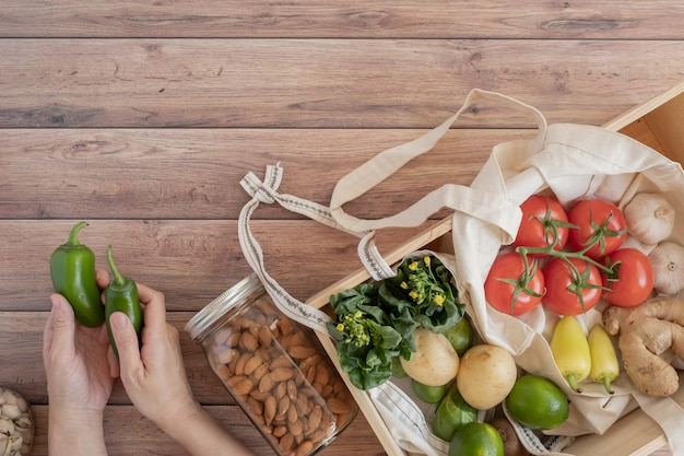 Ноль отходов жизни. хлопок сетчатая сумка со свежими овощами на деревянном столе плоской планировки. без пластика для покупки продуктов и доставки. Premium Фотографии