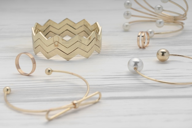 Zigzag shape golden bracelet between golden girl accessories on wooden table Premium Photo