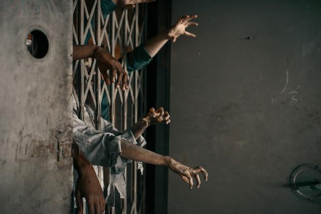ゾンビの手がエレベーターから突き出て、致命的な追跡。都市の恐怖、不気味な這う攻撃、終末の黙示録、血まみれモンスター Premium写真