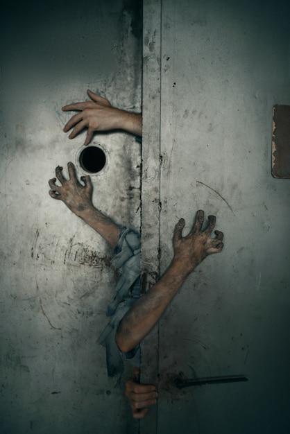 엘리베이터 문에서 좀비 손이 튀어 나와 치명적인 추격전. 도시의 공포, 소름 끼치는 크롤리 공격, 종말의 종말, 피 묻은 괴물 프리미엄 사진