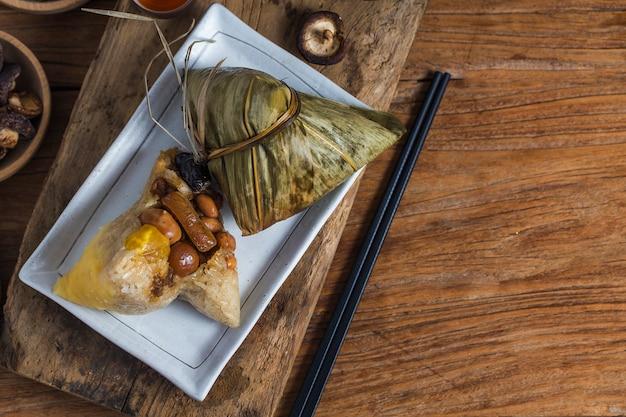 女性がドラゴンボートフェスティバルのプレゼントとして他人にzongzi(米団子)を贈っています Premium写真