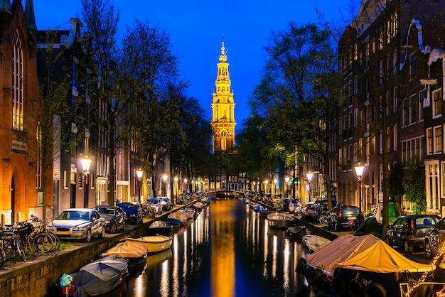 夜にオランダ、アムステルダムの街の運河の終わりにアムステルダムzuiderkerk教会の塔。 Premium写真