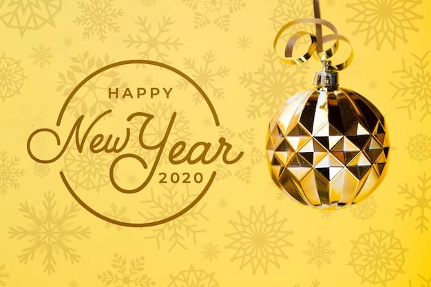 黄色の背景にゴールデンクリスマスボールと幸せな新年2020 無料 Psd