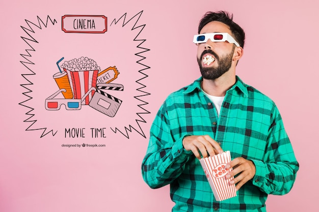 Бородатый молодой человек ест попкорн с 3-мя бокалами для кино рядом с нарисованными от руки элементами кино Бесплатные Psd