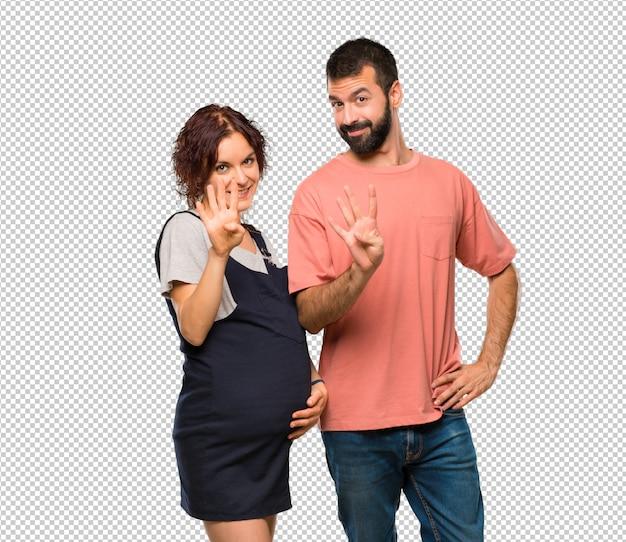 妊娠中の女性と幸せと4つの指で数えるカップル Premium Psd