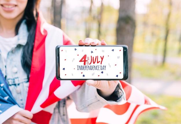 4 июля день независимости соединенных штатов америки. женщина держит смартфон Бесплатные Psd