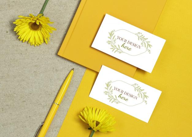 本、黄色のペンと夏の花のモックアップ名刺 Premium Psd