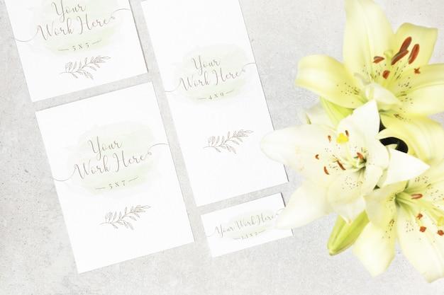 灰色の背景の上に花と結婚式のカードのパッケージ Premium Psd