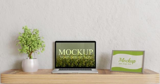 木製の机の上のノートパソコンのモックアップとフレームのモックアップを画面します。 Premium Psd