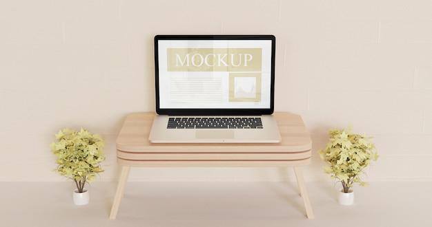 Экран ноутбука макет на деревянный настенный стол с декоративными коричневыми растениями Premium Psd