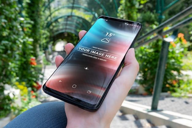 Женщина держит современный смартфон в парке макет Premium Psd