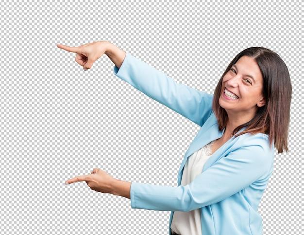 側に指している笑顔、自然でカジュアルな何かを提示する驚いた Premium Psd
